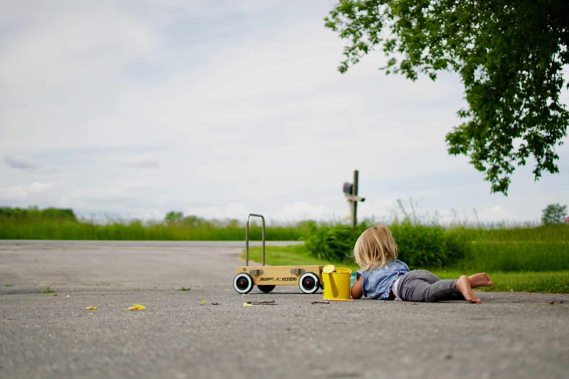 girl lying on road in front of cart -  encourage your child to explore